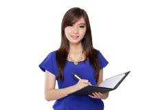 Pluma y cuaderno de tenencia asiática de la muchacha, aislados en blanco Foto de archivo libre de regalías