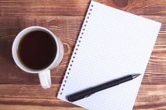 Pluma y cuaderno del café foto de archivo