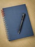 Pluma y cuaderno en el vector de madera Fotos de archivo