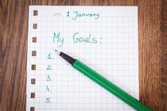 Pluma y cuaderno para planear resoluciones y metas de los Años Nuevos Foto de archivo