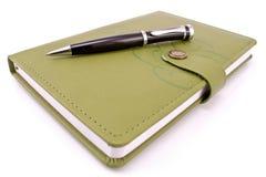 Pluma y cuaderno verde Fotos de archivo