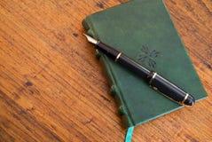 Pluma y diario en el escritorio de madera Imágenes de archivo libres de regalías