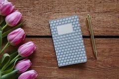 Pluma y diario listos para escribir la atmósfera de la primavera con los tulipanes rosados Foto de archivo