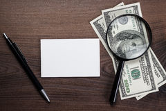 Pluma y dinero en blanco del cuaderno en la tabla Foto de archivo libre de regalías