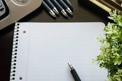 Pluma y documento sobre el escritorio de madera marrón con la planta Concepto del asunto Foto de archivo libre de regalías