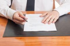 Pluma y documentos de ofrecimiento del hombre de negocios para firmar Imagenes de archivo