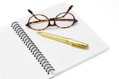 Pluma y lentes en un cuaderno Fotos de archivo