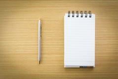 Pluma y libreta con la página en blanco Foto de archivo