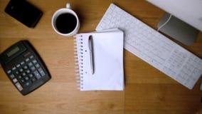 Pluma y libreta que caen sobre el escritorio de oficina