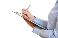 Pluma y lista de control de tenencia de la mano Fotografía de archivo libre de regalías