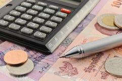 Pluma y monedas de la calculadora en billetes de banco Fotos de archivo libres de regalías