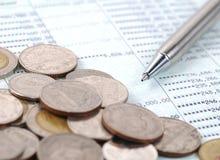 Pluma y monedas en cuenta bancaria Fotos de archivo libres de regalías