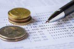 Pluma y monedas en la declaración de la cuenta bancaria Fotografía de archivo libre de regalías