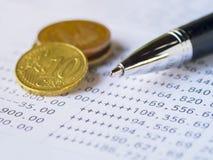 Pluma y monedas en la declaración de la cuenta bancaria Fotografía de archivo