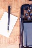 Pluma y papel por la máquina de escribir en la tabla Fotos de archivo libres de regalías