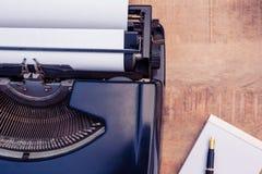 Pluma y papel por la máquina de escribir en la tabla de madera Imágenes de archivo libres de regalías
