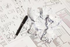 Pluma y papeles arrugados en gráficos de ingeniería. foto de archivo