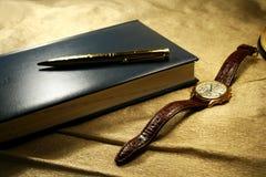 Pluma y reloj del cuaderno imagen de archivo