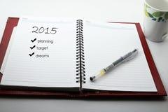 Pluma y taza de café y de cuaderno con un planeamiento para 2015 Foto de archivo
