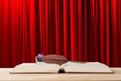 Pluma y tintero de la pluma de canilla del vintage en el libro abierto viejo contra fondo rojo de la cortina del teatro Historia, fotografía de archivo