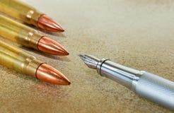 Pluma y tres balas Imágenes de archivo libres de regalías