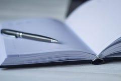 Pluma y un cuaderno en el lugar de trabajo Fotos de archivo