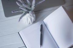 Pluma y un cuaderno en el lugar de trabajo Imagen de archivo libre de regalías
