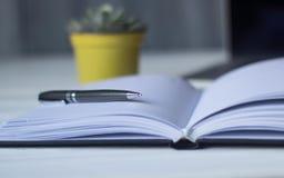 Pluma y un cuaderno en el lugar de trabajo Imagenes de archivo