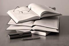 Pluma y vidrios abiertos de los libros Foto de archivo libre de regalías