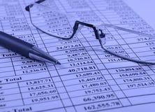 Pluma y vidrios en informe financiero Fotografía de archivo libre de regalías