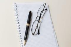 Pluma y vidrios negros con el cojín o la libreta blanco Fotos de archivo libres de regalías