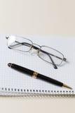 Pluma y vidrios negros con el cojín o la libreta blanco Imágenes de archivo libres de regalías