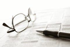 Pluma y vidrios sobre anuncios clasificados del periódico Fotografía de archivo