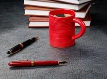 Plumas con una taza de café Imagen de archivo libre de regalías
