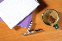 Plumas con una taza de café Foto de archivo