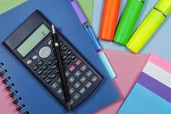 Plumas de la calculadora y del highlighter con un cuaderno Fotos de archivo libres de regalías