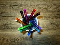 Plumas del color en una taza de cerámica imágenes de archivo libres de regalías