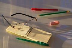 Plumas, lápiz, borrador y cuaderno con los vidrios Foto de archivo