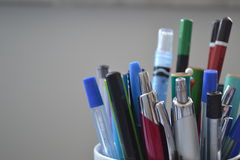 Plumas y lápices en soporte Imágenes de archivo libres de regalías