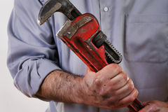 Plumber. Stock image of plumber in uniform holding pipe wrench Stock Image