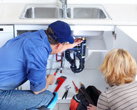Plumber. Mature plumber fixing a sink at kitchen Stock Images