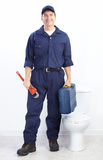 Plumber. Mature plumber near a flush toilet Stock Image