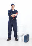 Plumber. Mature plumber near a flush toilet Stock Photography