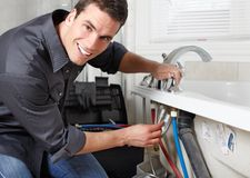 Plumber. Young plumber fixing a sink. Worker at kitchen Royalty Free Stock Photography