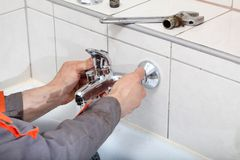 Plumber. Hands fixing water tap with spanner royalty free stock image