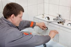 Plumber. Fixing water pipe in a bathroom royalty free stock image