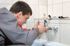 Plumber. Fixing water pipe in a bathroom royalty free stock images