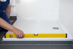 Plumber. Installs a shower tray in the bathroom Royalty Free Stock Images