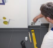 Plumber. Installs a heating system  in the bathroom Royalty Free Stock Images