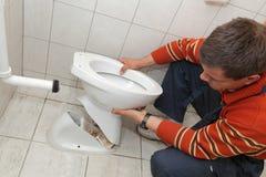 Plumber. Replacing broken toilet in a washroom royalty free stock photos